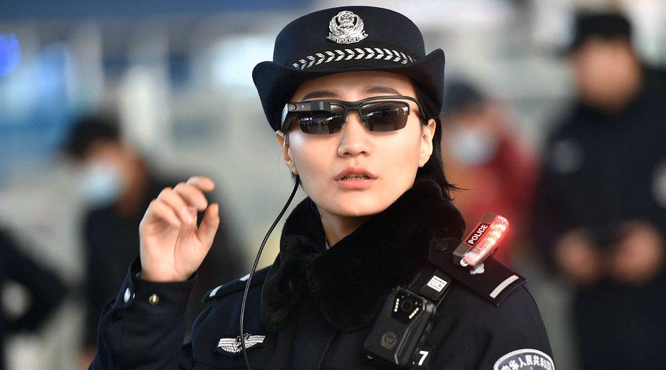 人工知能(AI)による顔認証システムと連動したメガネ型情報端末を使用する中国の警官(5日、河南省鄭州市 AFP=時事)