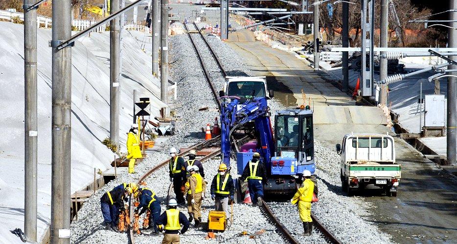 JR大野駅付近で常磐線の復旧工事に当たる作業員(16日、福島県大熊町=時事)