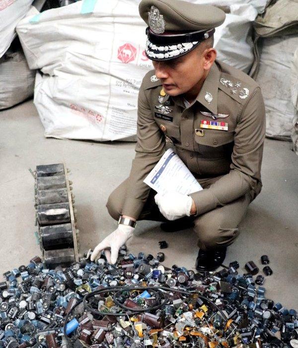 リサイクル工場を捜索し、電子廃棄物を調べるタイ警察幹部(15日、タイ中部パトゥンタニ県=時事)